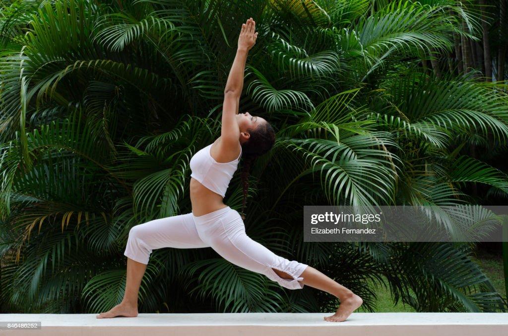 A woman doing a yoga pose on a garden : Stock Photo