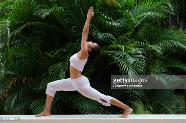 A woman doing a yoga pose on a garden