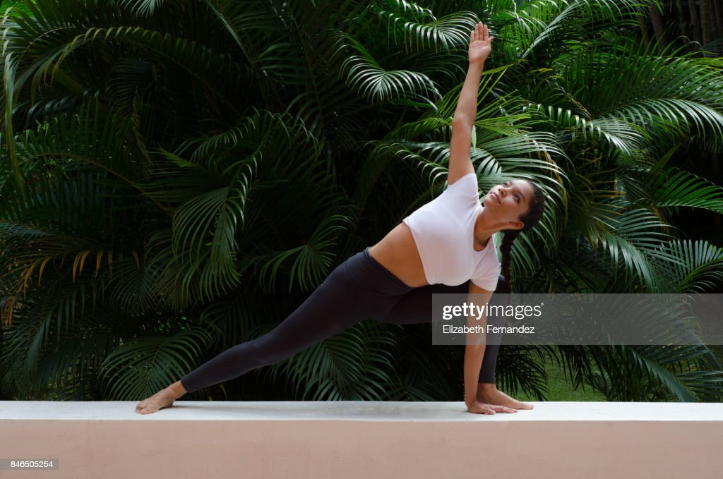 A woman doing a yoga pose on a garden : Stock Photo