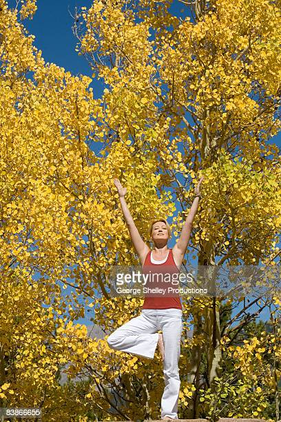 Woman doing a yoga tree outdoors in the Fall Aspen