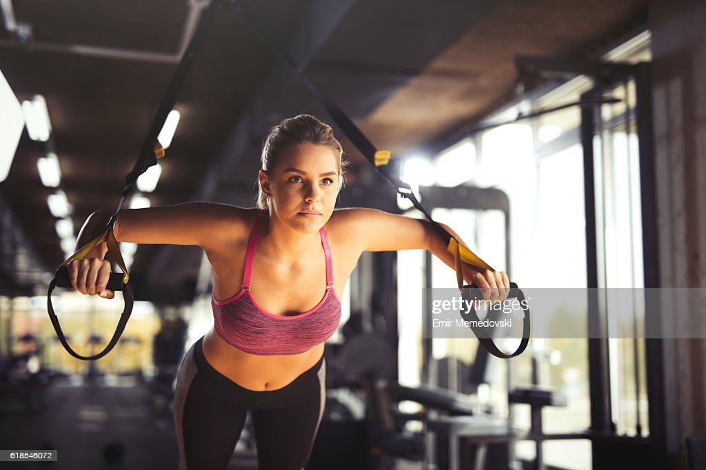 Woman doing arm exercises with suspension straps at gym. : Stock Photo