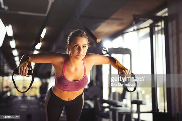 woman doing arm exercises with suspension straps at gym. - man made object stock pictures, royalty-free photos & images