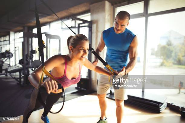 Woman doing arm exercises with suspension straps at gym.