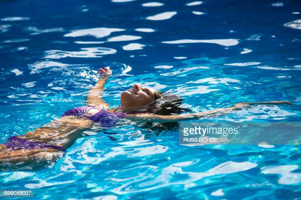 Woman doing backstroke in swimming pool