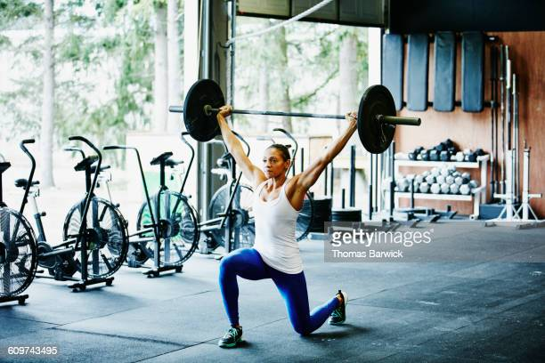 woman doing barbell lunges during workout - ウエイトトレーニング ストックフォトと画像