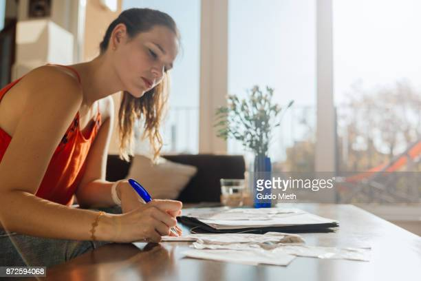 woman doing bookkeeping at home. - ersparnisse stock-fotos und bilder