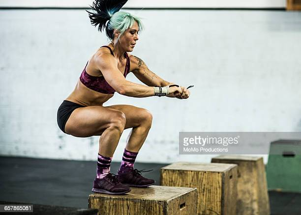 woman doing box jumps at crossfire gym - momo challenge stock photos and pictures