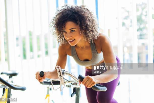 woman doing cardio exercises on a stationary bike at the gym - exercise bike stock photos and pictures
