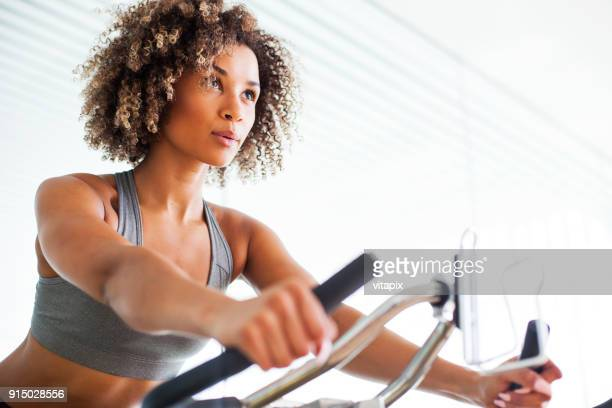 Woman Doing Cardio Exercises on a Stationary Bike at the Gym