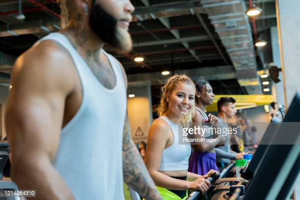 woman doing cardiovascular exercise on a treadmill and looking the camera - musculoso stock pictures, royalty-free photos & images