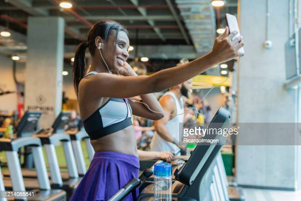 woman doing cardiovascular exercise on a treadmill and she take a selfie - musculoso stock pictures, royalty-free photos & images