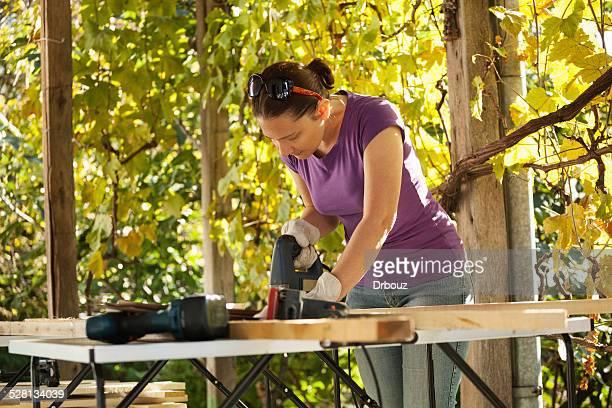 heimwerken-frau, die arbeitet im terrace tischlerarbeit - stichsäge stock-fotos und bilder