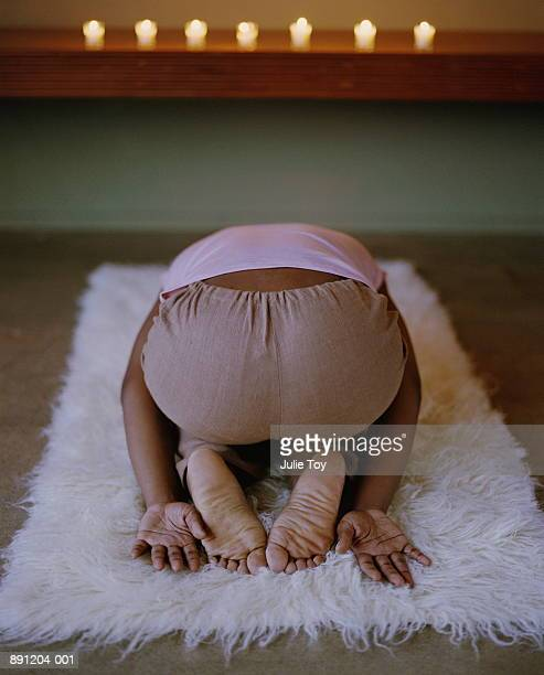 woman doing 'child's posture' on rug, in front of candle alter - soles pose stock pictures, royalty-free photos & images