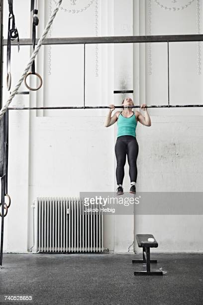 woman doing chin-up in cross training gym - chin ups stock photos and pictures