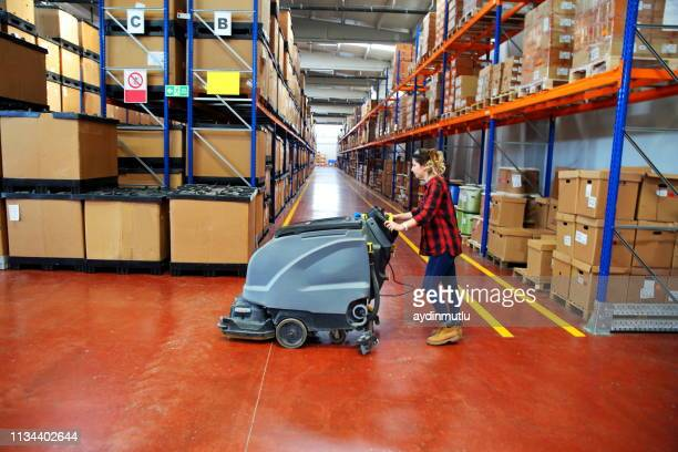woman doing cleaning in warehouse - pulito foto e immagini stock