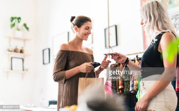 woman doing credit card purchase from saleswoman - clothing store stock pictures, royalty-free photos & images