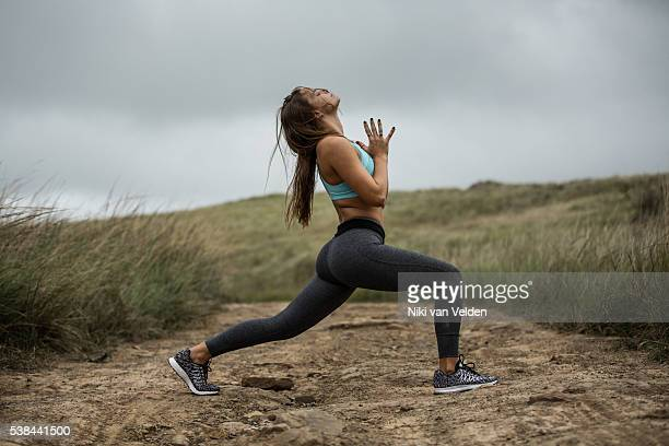 woman doing crescent lunge with hands at heart centre - yoga pants stock photos and pictures