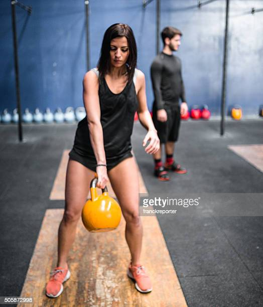 woman doing cross fitness exercise with kettlebell