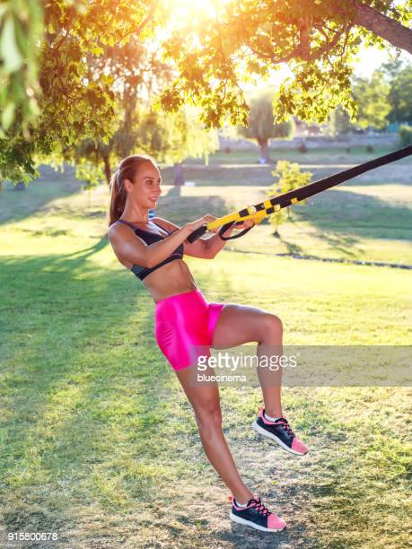 woman doing crossover reverse lunge with straps - strap stock photos and pictures