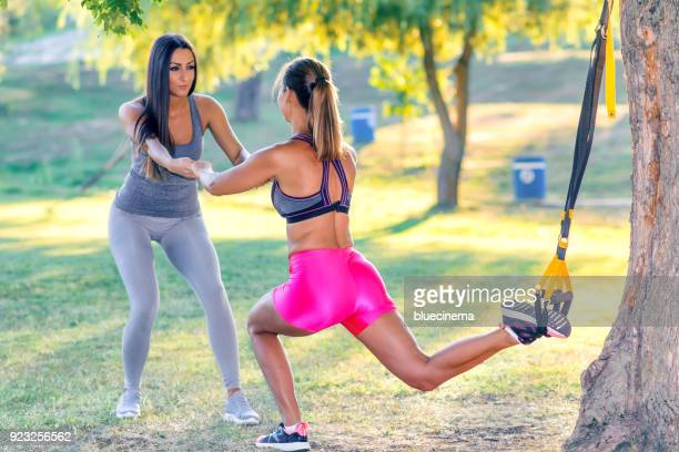 woman doing crossover reverse lunge with straps with instructor - body piercings stock photos and pictures