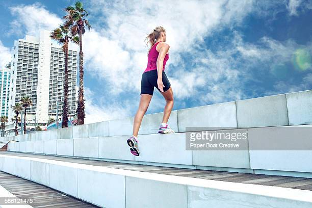 Woman doing exercise by large steps outdoors