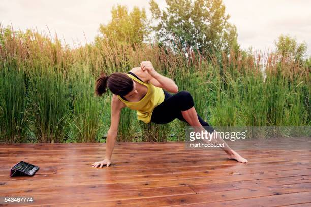 Woman doing exercises outdoors in summer with digital tablet.