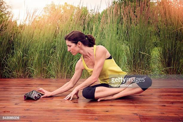 Frau Übungen im Freien im Sommer mit Digitaltablett.