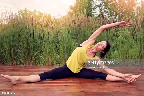 Frau tun stretching-Übungen im Freien im Sommer.
