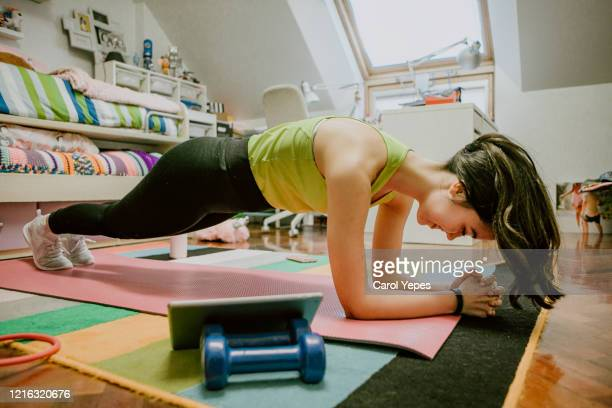 woman doing exercises through online videos at home - plank position stock pictures, royalty-free photos & images