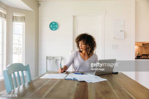 woman doing finances at home - usar portátil imagens e fotografias de stock