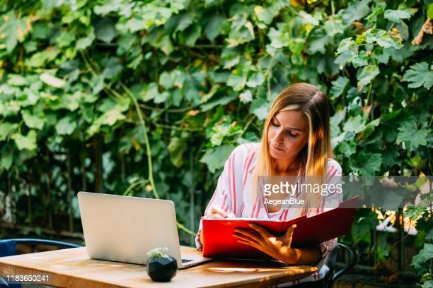 femme faisant le travail indépendant dans le jardin - travailleur indépendant photos et images de collection