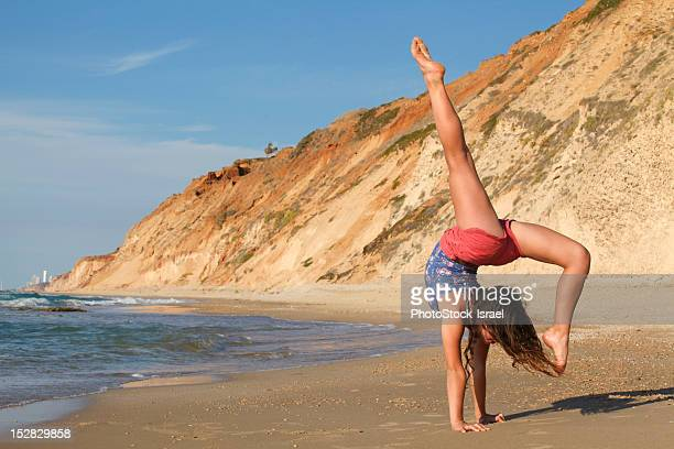woman doing gymnastics on beach - girl with legs spread stock photos and pictures