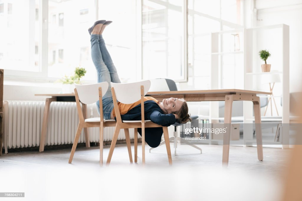 Woman doing gymnastics on chairs in a loft : Foto de stock
