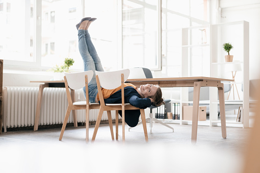 Woman doing gymnastics on chairs in a loft - gettyimageskorea