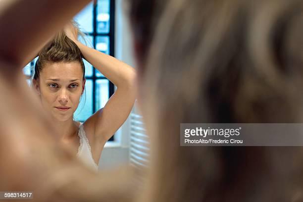 Woman doing hair in bathroom mirror