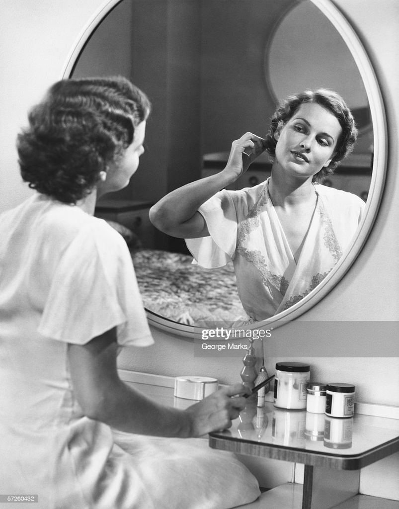 Woman doing hair in front of mirror, (B&W) : Stock Photo