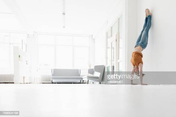 Woman doing handstand in a loft