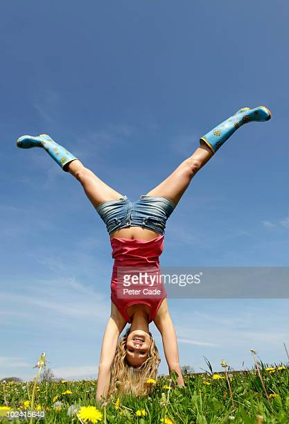 Woman doing handstand in field