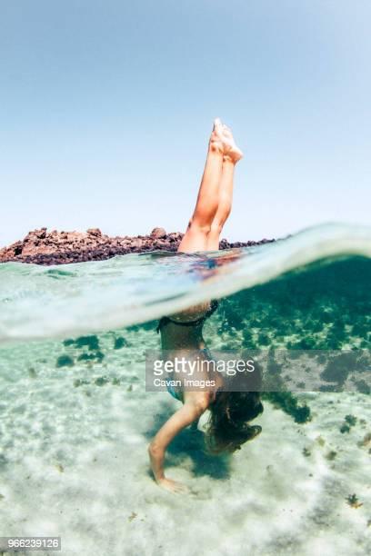 woman doing handstand in sea against clear sky - travel destinations imagens e fotografias de stock