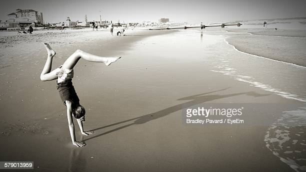 woman doing handstand on beach - pavard stock pictures, royalty-free photos & images