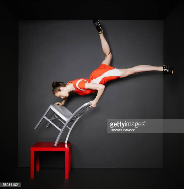 Woman doing handstand on chair balanced on table