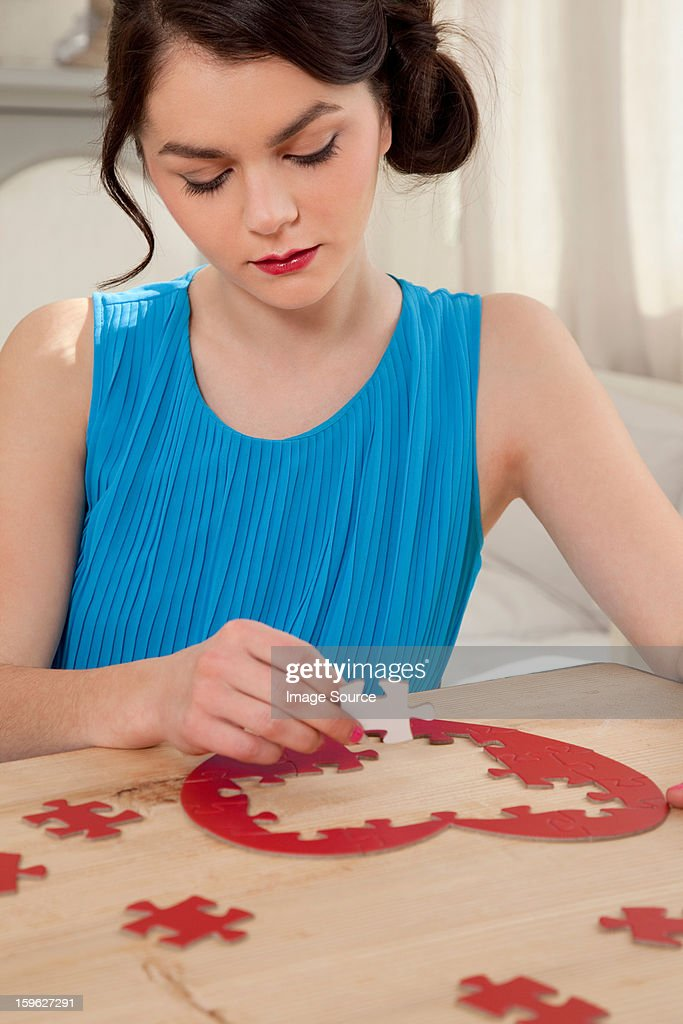 Woman doing heart shaped jigsaw puzzle : Stock Photo