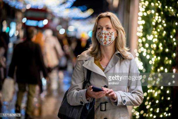woman doing her christmas shopping using her cell phone on the street - merchandise stock pictures, royalty-free photos & images