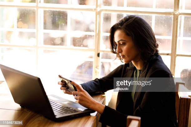 woman doing her finances at coffee shop - pardo brazilian stock pictures, royalty-free photos & images