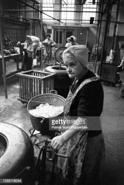 Woman doing her laundry in a communal washhouse in the East end of London, circa June 1969. From a series of images to illustrate the many...
