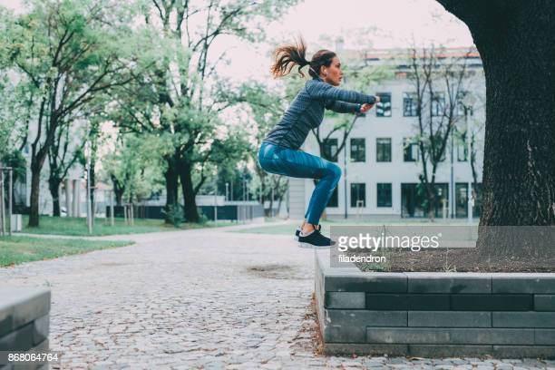 woman doing jumping squats - crouching stock pictures, royalty-free photos & images