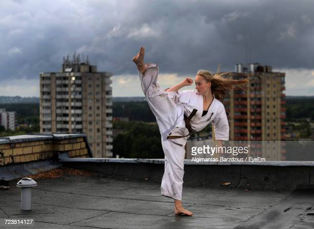 Woman Doing Karate On Rooftop In City