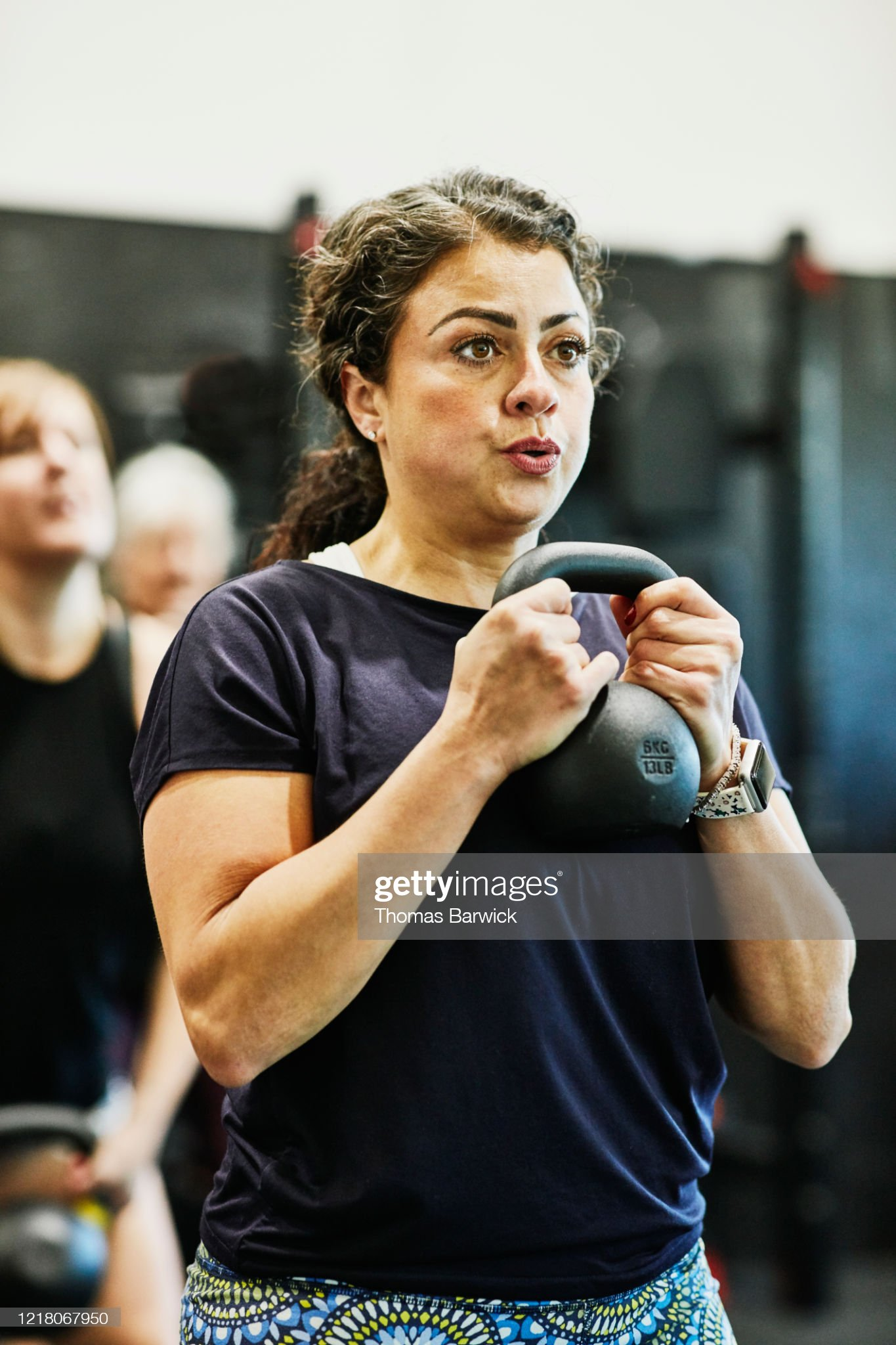Woman doing kettlebell squats during fitness class in gym : 圖庫照片