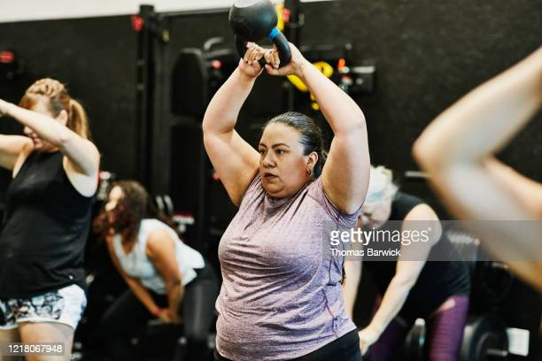 woman doing kettlebell swings while working out during class in gym - effort stock pictures, royalty-free photos & images