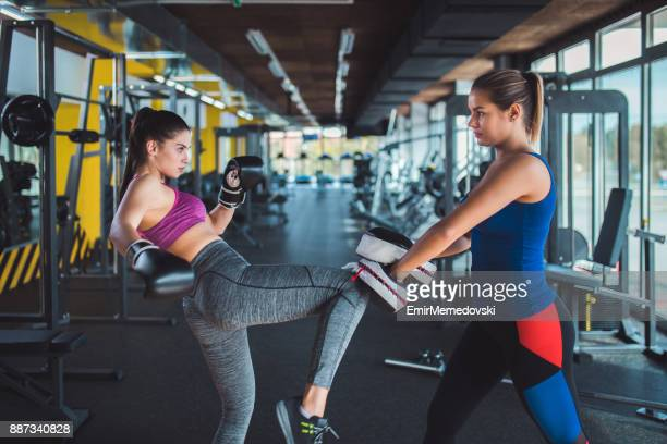 Woman doing kickboxing workout with her coach